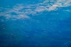 Взгляд земли от самолета над облаками Стоковая Фотография
