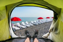 Взгляд изнутри шатра на loungers солнца на пляже Стоковое фото RF