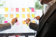 Взгляд команды дела на примечаниях прилипателя на стеклянной стене в meetin Стоковые Изображения