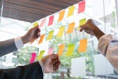 Взгляд команды дела на примечаниях прилипателя на стеклянной стене в meetin Стоковые Фотографии RF