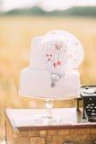 Взгляд конца-вверх белого свадебного пирога при воздушно-воздушный шар помещенный на винтажных чемоданах около части черноты Стоковое Фото
