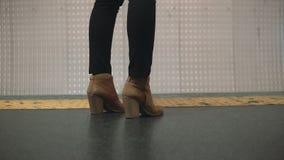 Взгляд конца-вверх ботинок ноги женщины нося в платформе метро Девушка стоя около рестриктивной линии и ждать поезда Стоковое Фото