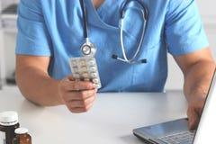 Взгляд конца-вверх женской руки доктора держа бутылку с пилюльками и писать рецепт Здравоохранение, медицинская концепция фармаци Стоковое Фото