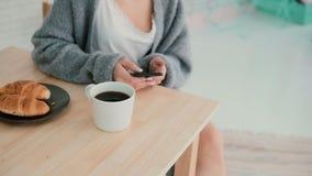 Взгляд конца-вверх женщины имея завтрак и интернет просматривать, используя сенсорный экран Девушка читает новую на smartphone Стоковое фото RF