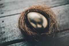 Взгляд конца-вверх золотого пасхального яйца в гнезде на деревянном столе Стоковая Фотография