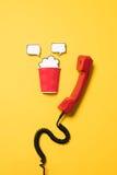Взгляд конца-вверх красных телефонной трубки и бумажного стаканчика с речью клокочет Стоковые Изображения RF