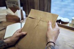 Взгляд конца-вверх мужских рук держа коричневый конверт на деревянном столе стоковые изображения