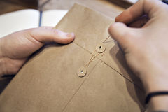 Взгляд конца-вверх мужских рук держа коричневый конверт с кофе на деревянном столе Стоковые Изображения
