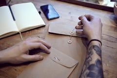 Взгляд конца-вверх мужчины татуировал руки с взгляд сверху конвертов, книги и телефона Стоковое фото RF