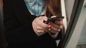 Взгляд конца-вверх руки женщины держа smartphone, сидя публично переход Прибой девушки интернет с сенсорным экраном Стоковое Фото