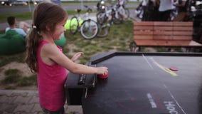Взгляд конца-вверх счастливой маленькой девочки играя хоккей воздуха с отцом Конкуренция между папой и дочерью сток-видео