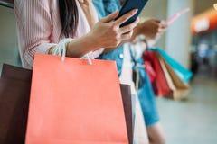 Взгляд конца-вверх частично женщины с хозяйственными сумками используя smartphone Стоковая Фотография RF
