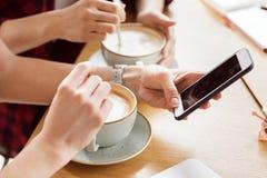 Взгляд конца-вверх частично молодых женщин сидя на таблице и выпивая кофе Стоковые Изображения RF