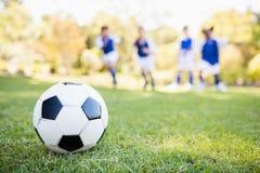 Взгляд крайности близкий поднимающий вверх воздушного шара футбола против предпосылки детей Стоковое фото RF