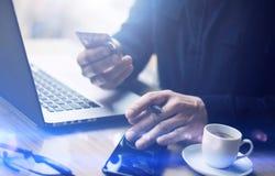 Взгляд крупного плана бизнесмена держа кредитную карточку в руке и используя smartphone, портативный компьютер на деревянном стол Стоковое Изображение