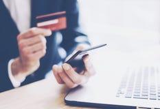 Взгляд крупного плана бизнесмена держа кредитную карточку в руке и используя smartphone, портативный компьютер на деревянном стол Стоковое фото RF