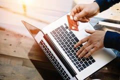 Взгляд крупного плана бизнесмена держа пластичную кредитную карточку в руке и используя компьютер-книжку для онлайн покупок пока Стоковое Изображение