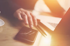 Взгляд крупного плана бизнесмена указывая палец на экране smartphone Элегантный сотрудник работая на солнечном офисе на компьтер- Стоковое фото RF