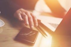 Взгляд крупного плана бизнесмена указывая палец на экране smartphone Элегантный сотрудник работая на солнечном офисе на компьтер- Стоковая Фотография