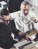 Взгляд крупного плана бородатого человека работая вместе с взрослым коллегой бизнесмена на деревянном столе вектор людей jpg иллю Стоковое Изображение RF