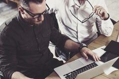 Взгляд крупного плана бородатого человека работая вместе с взрослым коллегой бизнесмена на деревянном столе вектор людей jpg иллю Стоковые Фото