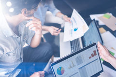 Взгляд крупного плана группы в составе молодые сотрудники работая совместно в современной студии офиса Бизнесмены обсуждая новый  Стоковая Фотография
