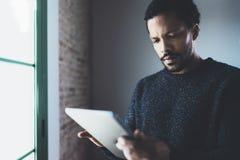 Взгляд крупного плана задумчивого бородатого африканского человека используя таблетку пока стоящ около окна в его современной ква Стоковое фото RF