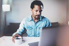 Взгляд крупного плана задумчивого бородатого африканского человека используя компьтер-книжку дома пока кофе выпивая чашки черный  Стоковое Фото