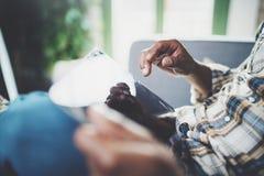 Взгляд крупного плана молодого американского африканского человека используя таблетку пока сидящ на софе дома Люди концепции рабо Стоковое фото RF