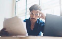 Взгляд крупного плана молодого бизнесмена работая на солнечном месте работы на компьтер-книжке пока сидящ на деревянном столе зап Стоковое Изображение RF
