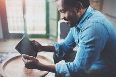Взгляд крупного плана молодого бородатого африканского человека используя таблетку пока сидящ на софе дома Люди концепции работая Стоковое Изображение