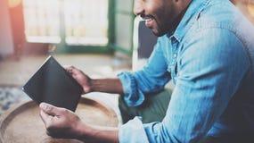 Взгляд крупного плана молодого бородатого африканского человека используя таблетку пока сидящ на софе дома Люди концепции работая Стоковая Фотография RF