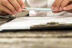Взгляд крупного плана мужских рук держа карандаш над обработкой документов на зажиме Стоковое фото RF