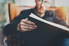 Взгляд крупного плана мужских рук держа черную книгу Молодой бородатый человек ослабляя дома пока сидящ в винтажном стуле Стоковые Изображения RF