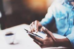 Взгляд крупного плана мужских рук касаясь мобильному телефону Африканский человек используя smartphone пока сидящ на деревянном с Стоковая Фотография