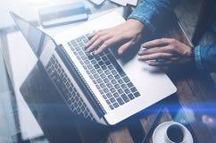 Взгляд крупного плана мужских рук печатая клавиатуру компьтер-книжки Современная тетрадь, чашка черного кофе и smartphone на дере Стоковая Фотография