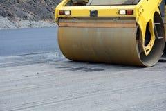 Взгляд крупного плана на ролике дороги работая на новом месте строительства дорог отремонтируйте дорогу Стоковое Фото