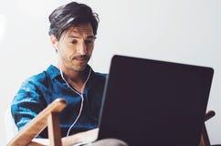 Взгляд крупного плана привлекательного усмехаясь человека работая дома Человек используя современные компьтер-книжку и наушники п Стоковое фото RF