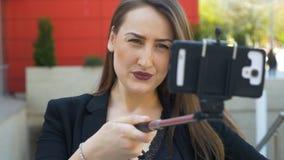 Взгляд крупного плана славной девушки представляет и делает смешные стороны с камерой smartphone и ручкой selfie акции видеоматериалы