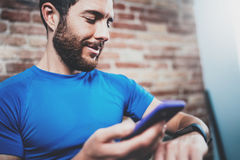 Взгляд крупного плана усмехаясь мышечного красивого спортсмена проверяя спорт приводит к на применении smartphone и умном вахте п Стоковое Изображение RF