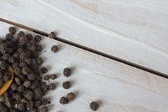 Взгляд крупного плана corns и ложки черного перца на деревянной предпосылке Стоковые Изображения RF
