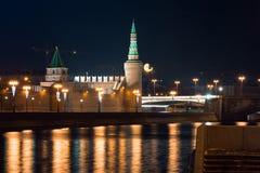 Взгляд к обваловке реки, стены Москвы Кремля и башни с полнолунием на предпосылке от другой стороны реки Стоковое Изображение RF