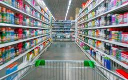 Взгляд магазинной тележкаи на междурядье и полках супермаркета - изображение имеет малую глубину поля стоковые изображения rf