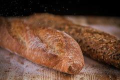 Взгляд макроса 2 свежих хрустящих хлебов багета с семенами подсолнуха и другими семенами на деревенском деревянном столе Стоковая Фотография RF