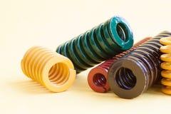 Взгляд макроса спиральных пружин металла Цвет краски желтого зеленого цвета краснокоричневый закручивает в спираль на желтой пред Стоковое фото RF
