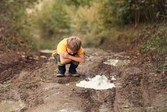 Взгляд мальчика в лужицу на проселочной дороге Стоковые Изображения