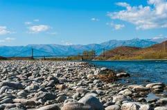 Взгляд моста через реку горы с каменистым берегом Стоковые Изображения RF