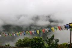 Взгляд молитвы сигнализирует на Trongsa Dzong с туманными холмами, Bumthang, Bhuta Стоковая Фотография