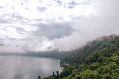 Взгляд наклонов, лесов и домов озера Albano на пасмурный и туманный день Стоковые Фотографии RF