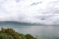 Взгляд наклонов, лесов и домов озера Albano на пасмурный и туманный день Стоковые Изображения